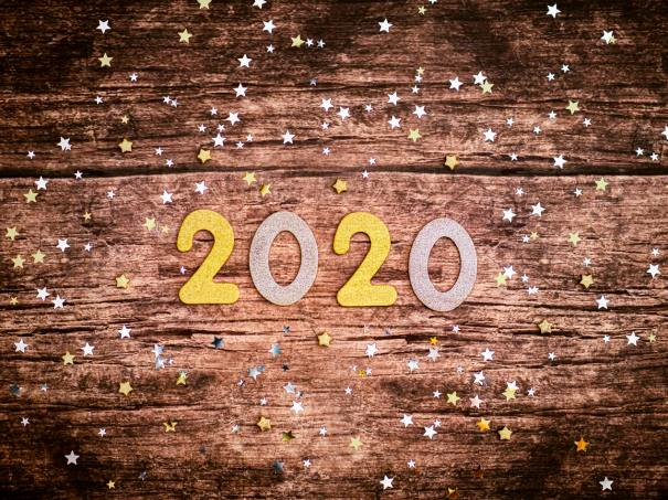 Picture of 2020 cut out numbers on a wood floor with confetti