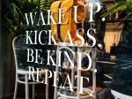 Storefront window that reads: Wake Up. Kick Ass. Be Kind. Repeat.